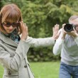 Stock Photo: Paparazzi takes picture from woman