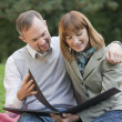 Couple with photo album outdoors — Stock Photo