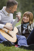 Man playing acoustic guitar outdoors — Stock Photo