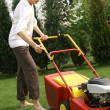 Woman mowing grass - Stock Photo