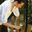 Woman painting wooden fence — ストック写真