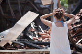 Woman in front of burned out house — Photo
