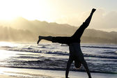 Man turns cartwheels on the beach — Stock Photo