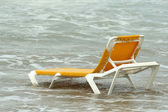 Chaise longue in water — Stock Photo