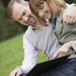 Couple watching photo album outdoors — Stock Photo