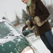 Woman scrubbing car in winter — Stock Photo