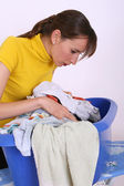 Woman and basket with dirty clothing — Stock Photo