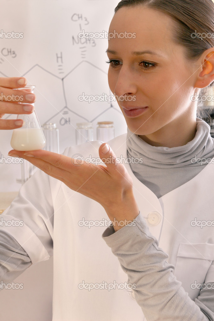 Chemist holding erlenmeyer flask containing white chemical — Stock Photo #1597928
