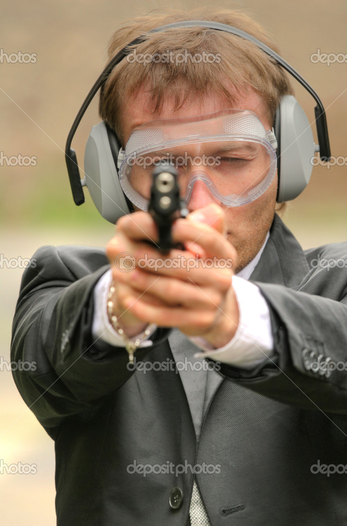 Businessman aiming with a gun into the camera — Stock Photo #1598271