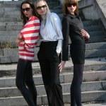 Three fashion women on the stairs — Stock Photo