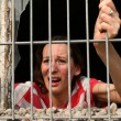 Royalty-Free Stock Photo: Woman behind bars crying