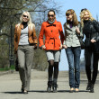Four friends walking on the street — Stock Photo