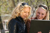 Women with laptop in park — Stock Photo