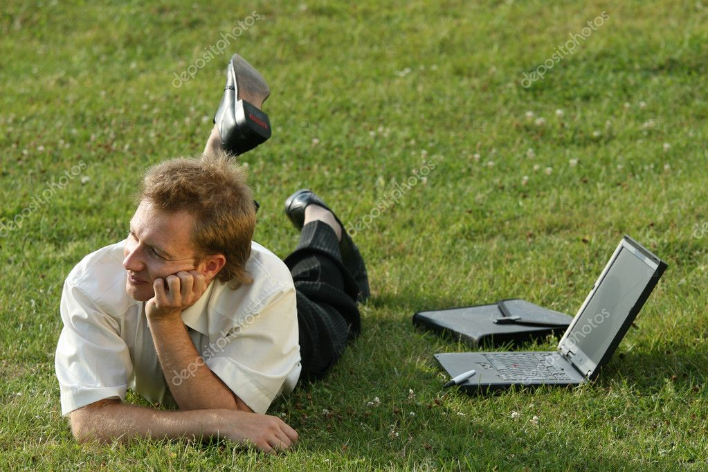 Relaxing businessman lying on the grass — Stock Photo #1955843