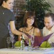 Waitress taking order from couple — Stockfoto