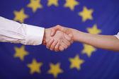 Hand shake over european flag — Stock Photo