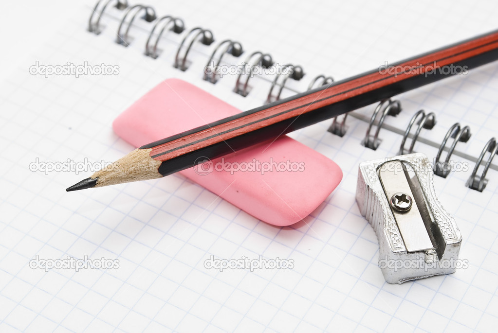 Sharpener and pencil with eraser on workbook page — Stock Photo #1606411