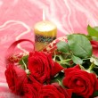 Roses and a candle — Stock Photo