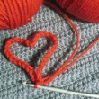 Knitted heart and red clews — Stock Photo