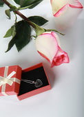 Rose and gift with jewelry decoration — Stock Photo