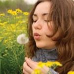 Beautiful woman blowing dandelion seeds — Stock Photo