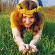 Girl in a wreatht from dandelions on a g — Stock Photo