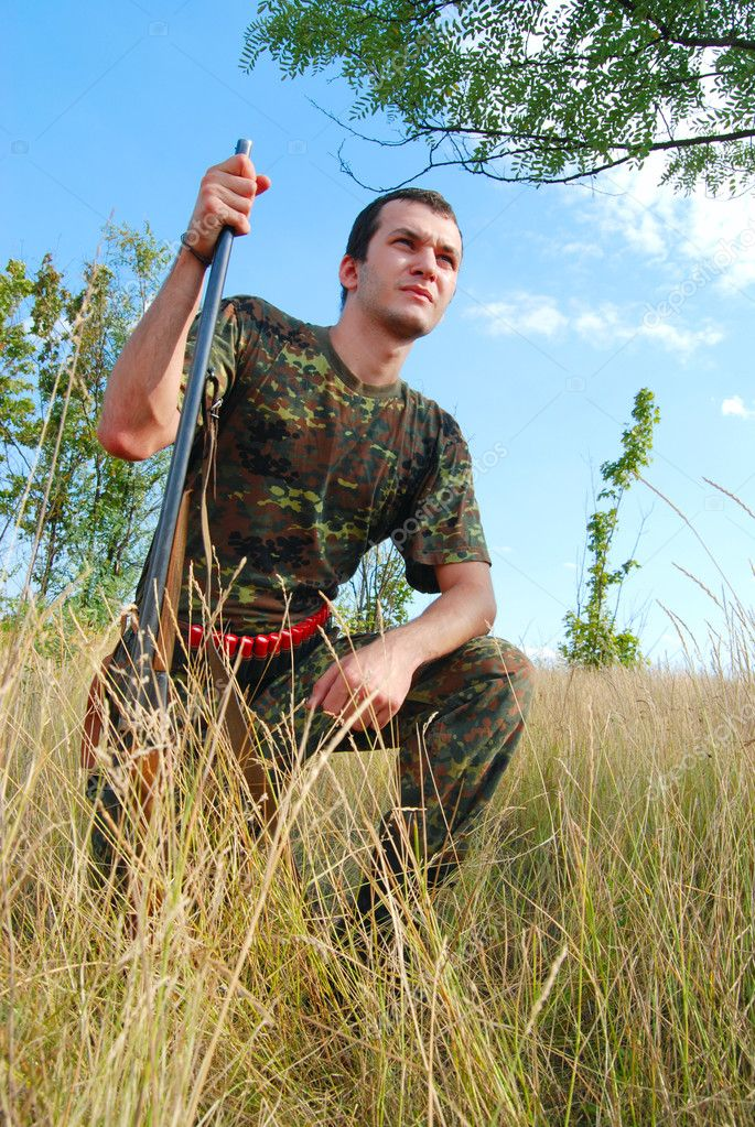 Hunter in camouflage with rifle at ready — Stock Photo #1565553