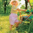 Girl in the forest near baby carriage — Stockfoto