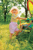 Girl in the forest near baby carriage — Stock Photo