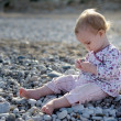 Little baby sitting on the stones by the — Stock Photo #1799147