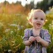 Little nice smiling baby in a meadow — Stock Photo