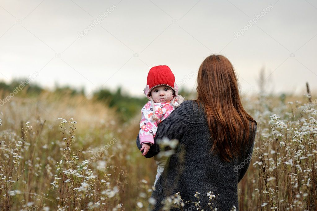 Mother is carryng her little baby girl accross the meadow  Stock Photo #1799144