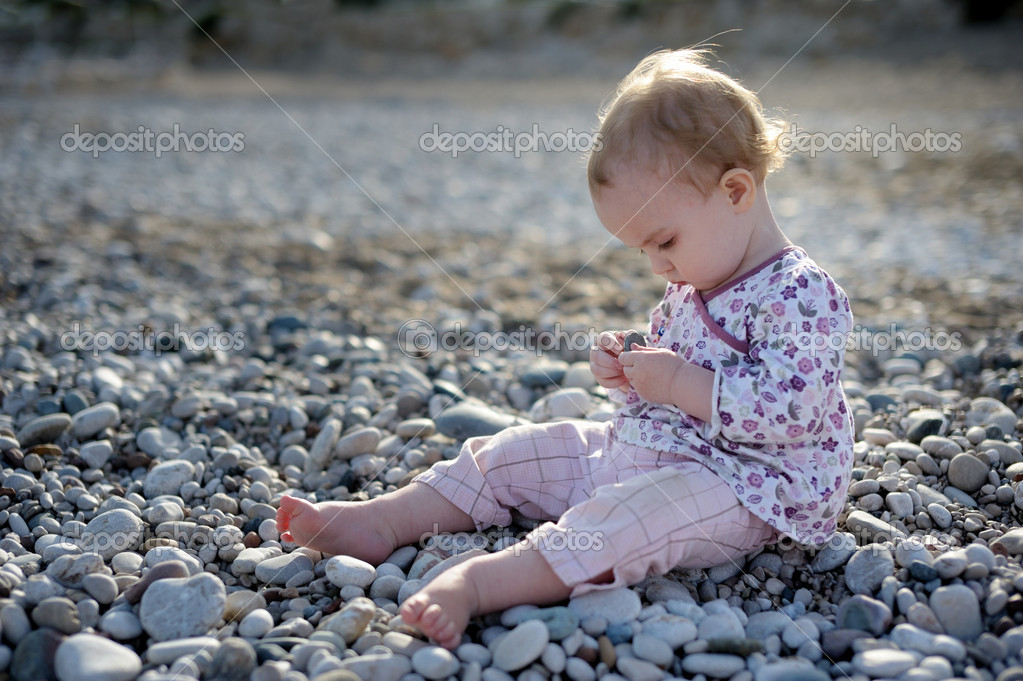 Little baby sitting on the stones by the sea and playing with those stones — Stock Photo #1799147