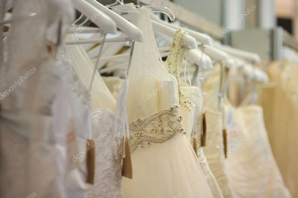 A few beautiful wedding dresses hanging on the stand — Stock Photo #1799219
