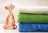 Bath towels and figurine of cats — Stock Photo