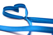 Tied blue ribbon forming shape of heart — Stock Photo