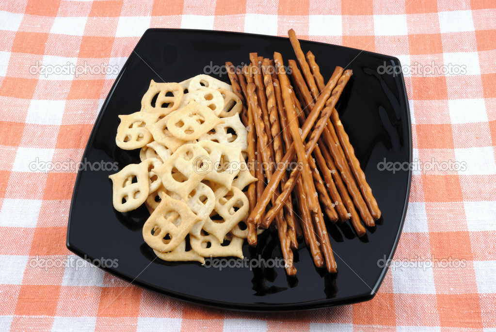 Mini crackers and salty grain sticks to beer on a black plate — Stock Photo #1238086