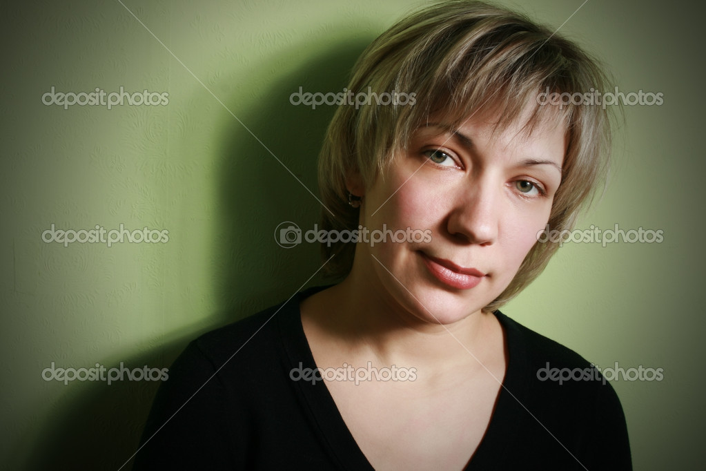 Portrait of the mature woman on a green background.  Stock Photo #1272906