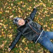 The boy lays on the ground covered by au — Stock Photo #1559421