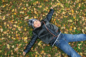 The boy lays on the ground covered by au — Stock Photo