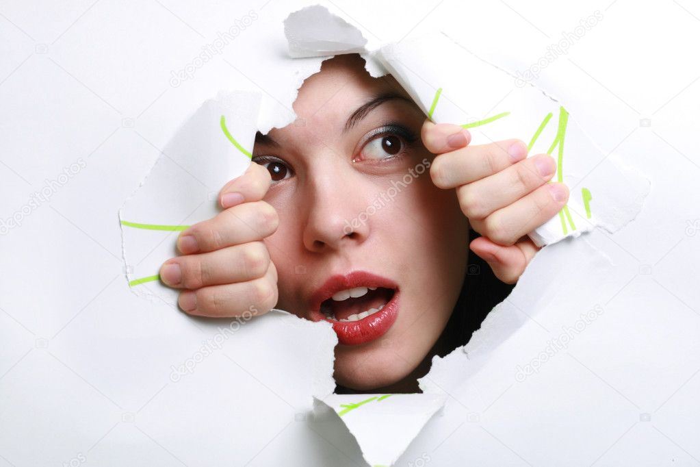 The girl spies through a hole in a paper.  Stock Photo #2506667