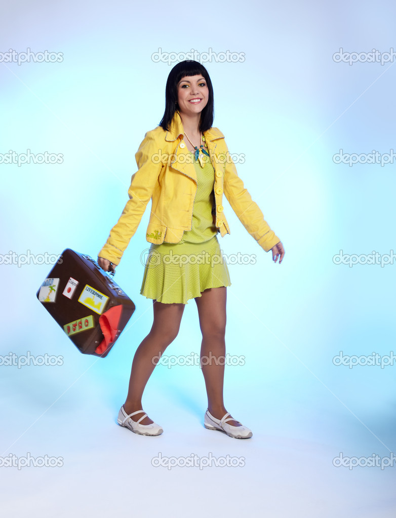 Portrait of beautiful brunette girl posing on blue with luggage — Stock Photo #1207233