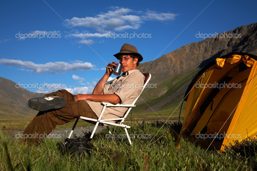 Man is sitting in the chair at the camp in mountains — Stock Photo #1301625
