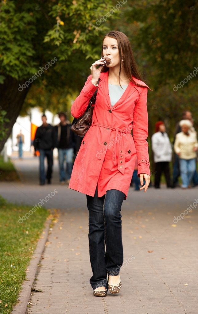 Girl walking along footpath and eating chocolate icecream — Stock Photo #1358618