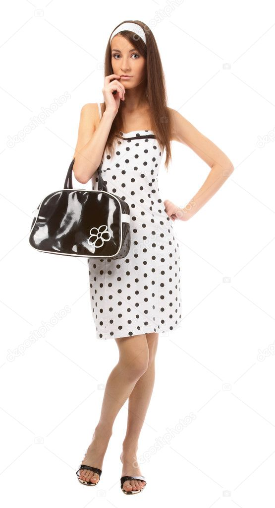 Beautiful model in polka-dot dress with black bag tries to recall something — Stock Photo #1358661