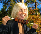 Smiling girl with shashlik — Stock Photo