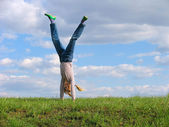 Somersault on grass on the sky&clouds background — Stock Photo