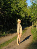 Girl walking away along the forest road — Stock Photo
