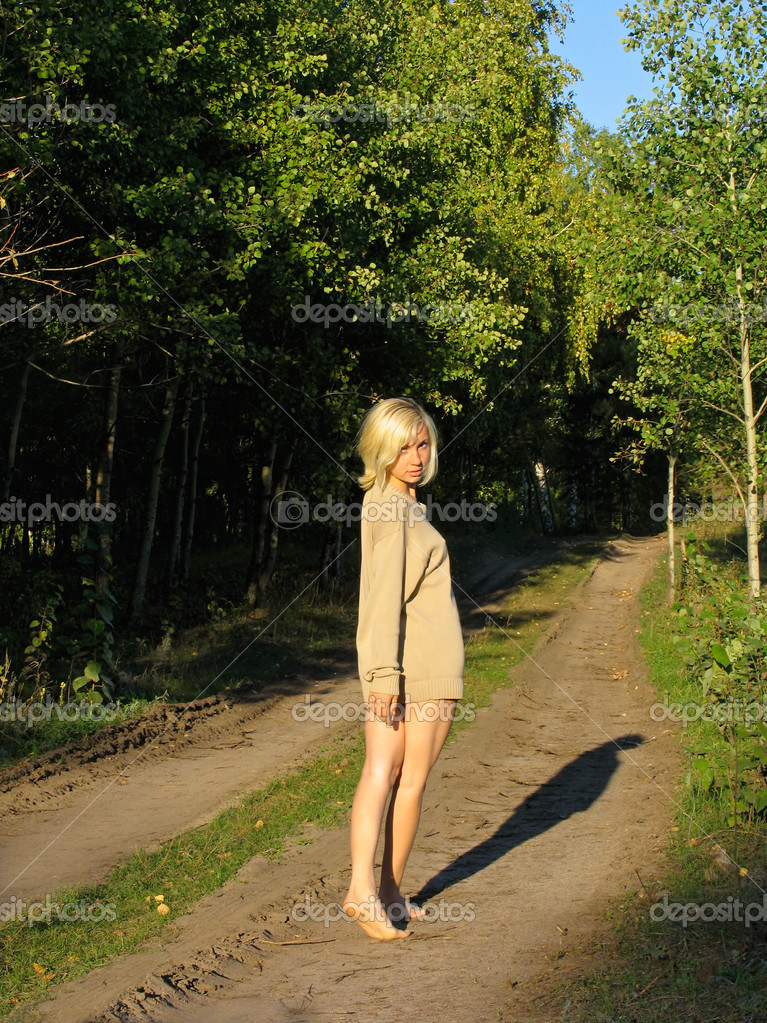 Blonde girl walking away along the forest road — Stock Photo #2630230