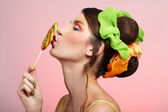 Beautiful model kissing lollipop — Stock Photo